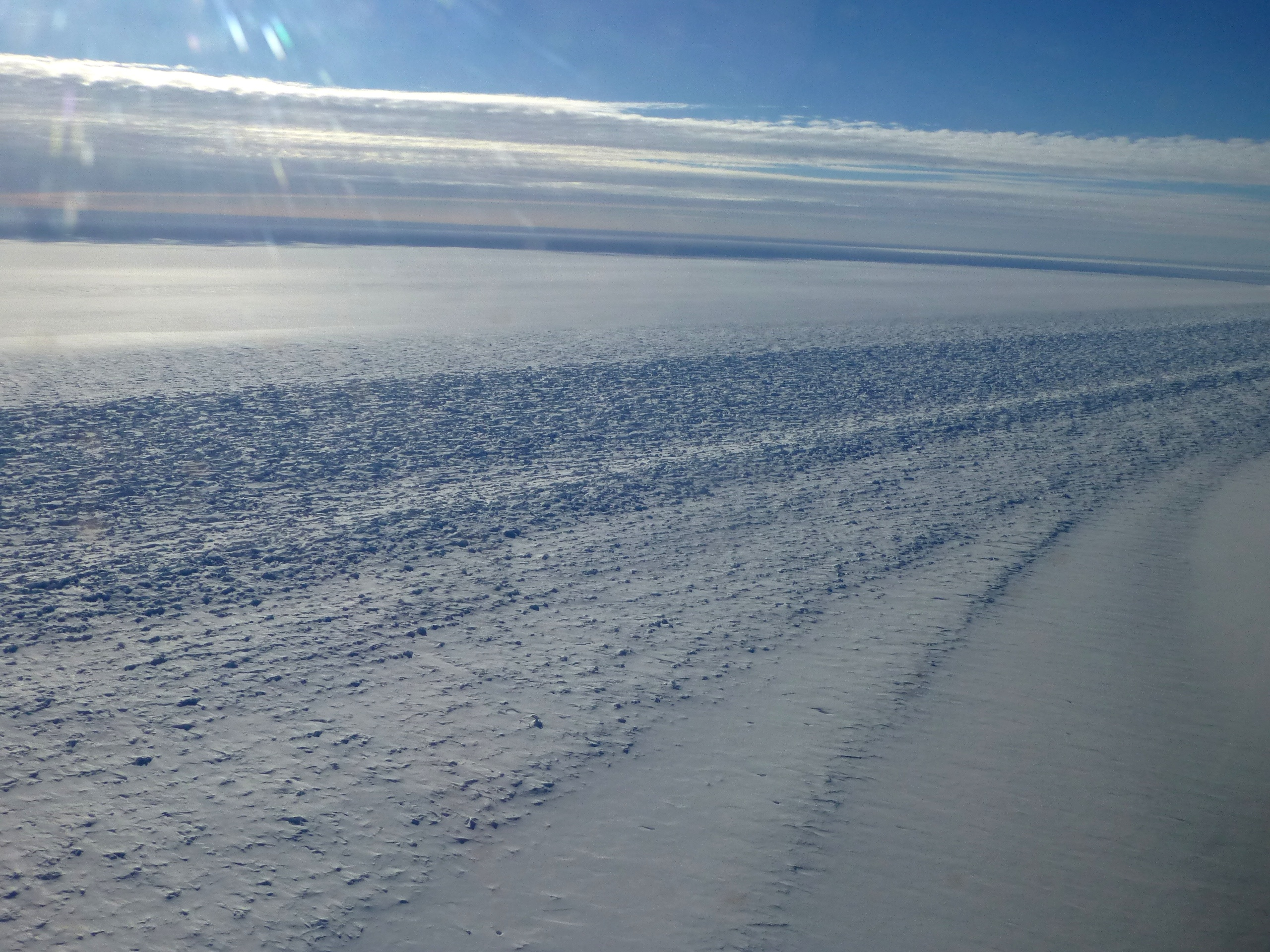 View of a glacier shear margin seen from the NASA DC-8 on the Nov. 1 survey of the Ronne Ice Shelf grounding line. A shear margin is the point where fast-flowing glacier ice meets slow-moving ice or rock (in this case, ice attached to the Dufek Massif in Antarctica's Pensacola Mountains). Credit: NASA / Maria-Jose Viñas