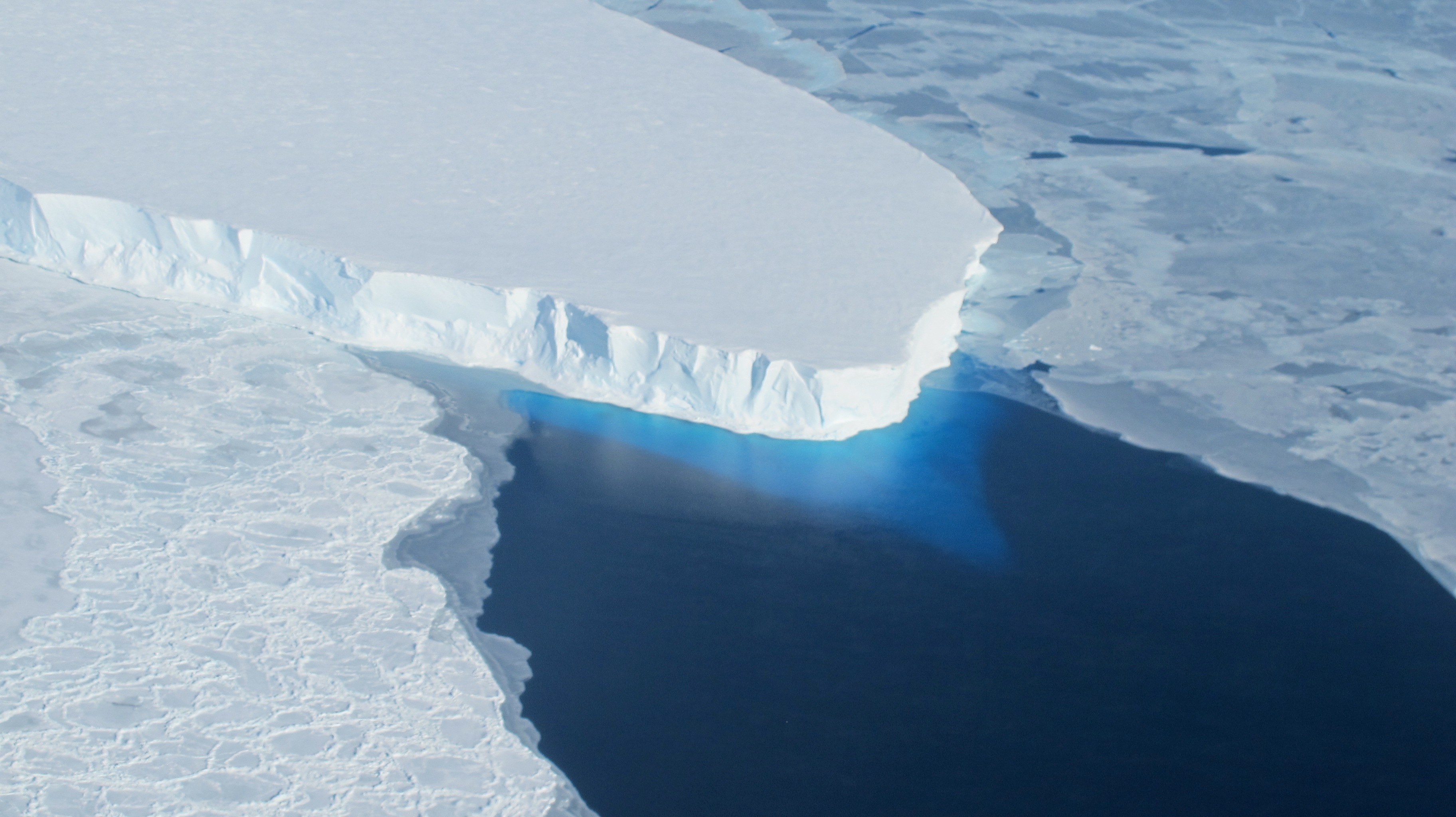The calving front of Thwaites Ice Shelf looking at the ice below the water's surface. Note how the water acts as a blue filter. Credit: NASA / Jim Yungel